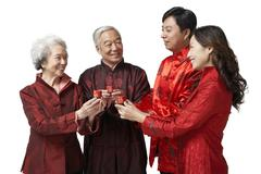 A daughter and her husband share a toast with her parents on Chinese New Year Stock Photos