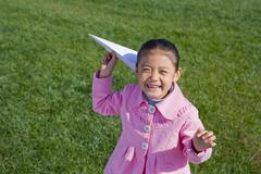 A young girl throwing a paper airplane Stock Photos