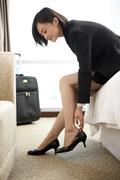 Woman in business attire putting on her shoes Stock Photos