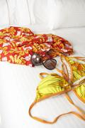Bikini, swimming trunks and sunglasses on a bed - stock photo