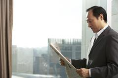 Man in business attire reading newspaper Stock Photos