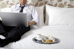 Cookies and coffee next to man in business attire Stock Photos