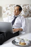 Man in business attire with laptop and tray of cookies and coffee Stock Photos