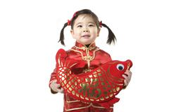 Young girl holding Chinese New Year fish Stock Photos