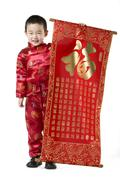 Boy in Chinese traditional clothes holding Chinese New Year scroll Stock Photos