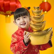 Girl in Chinese traditional clothes holding gold ingot Stock Photos