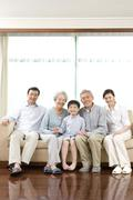 Stock Photo of Grandparents and Parents pose with son on sofa
