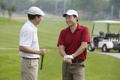 Two golfers chatting on the course - stock photo