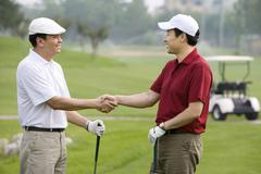 Two golfers shaking hands on the course - stock photo