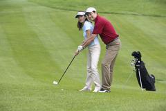 Golf coach teaching playing golf - stock photo