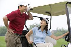 Two Golfers chatting by a golf cart - stock photo