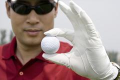 Lähikuva golfpallon golfarin kädessä Kuvituskuvat