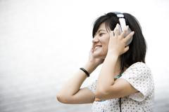 Young woman listening to music on headphones Stock Photos
