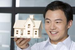 Stock Photo of Young man holding a house model