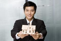 Young man holding a house model Stock Photos