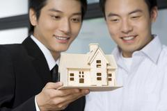 Real estate agent selling a house to customer - stock photo