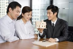 Real estate agent selling a house to customers - stock photo