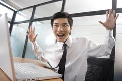 Young businessman get surprised by laptop - stock photo