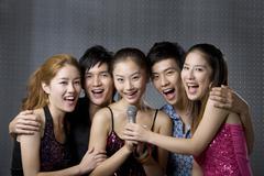 Young adults singing karaoke - stock photo