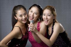 Young women singing karaoke - stock photo
