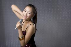 Young woman singing karaoke - stock photo