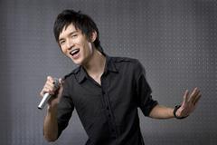 Young man singing karaoke - stock photo
