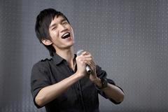 Stock Photo of Young man singing karaoke