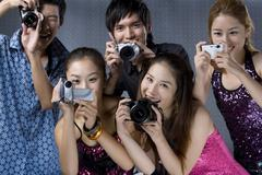 Young adults using digital cameras - stock photo