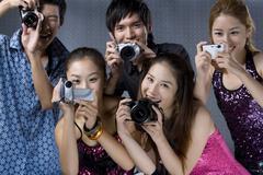 Young adults using digital cameras Stock Photos