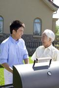 Father and son chatting in front of house - stock photo