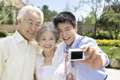 Family taking photos by digital camera Stock Photos