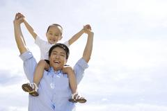 Stock Photo of Father carrying son on shoulder