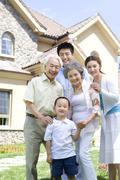 Three generation family in front of house - stock photo