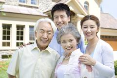 Stock Photo of Family of four in front of house