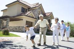 Three generation family walking by a house Stock Photos