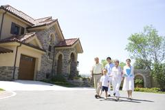 Stock Photo of Three generation family walking by a house