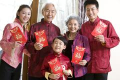 Family holding Chinese red envelope - stock photo