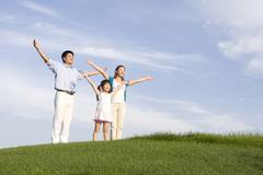 Family of three standing on the grass, arms out-stretched - stock photo