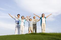 Family standing on the grass, arms out-stretched - stock photo