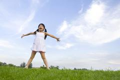 Girl standing in grass field, arms out-stretched Stock Photos