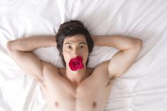 Naked Asian man on bed with rose - stock photo