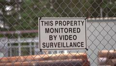 Fence with sign warning that property is being monitored Stock Footage