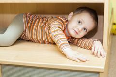 Child boy hiding in cupboard Stock Photos