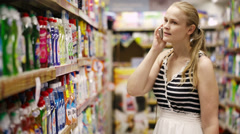 Woman chatting on her mobile while out shopping Stock Footage