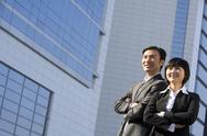 Stock Photo of Businessman and businesswoman standing in front of tall building