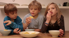A day in the life of home - Three siblings eating corn chips - stock footage