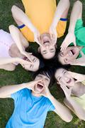 A group of young people shouting in a circle - stock photo
