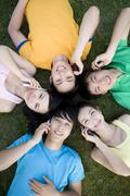 A group of young people in a circle using their mobile phones - stock photo