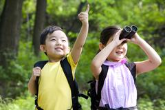 Brother and sister bird watching - stock photo