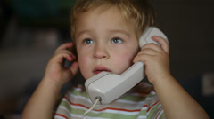 Excited little boy talking over telephone receiver Stock Footage